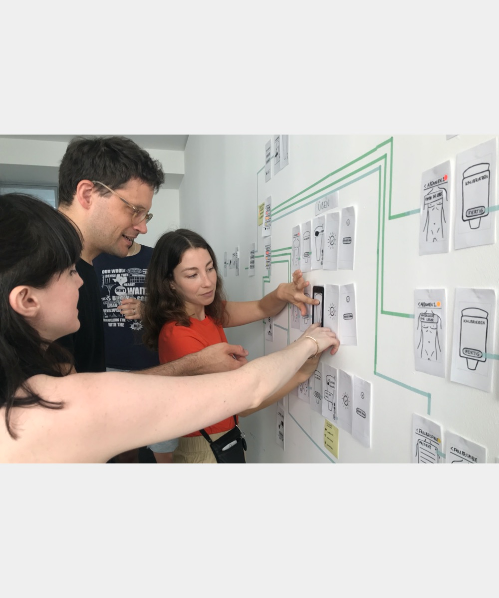 Three team members work together on the whiteboard
